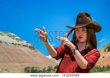 girl cowboy holds his fingers like a gun