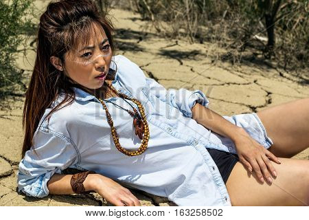 girl lying in the desert  with cracked earth
