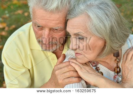 Portrait of a sad senior couple in park