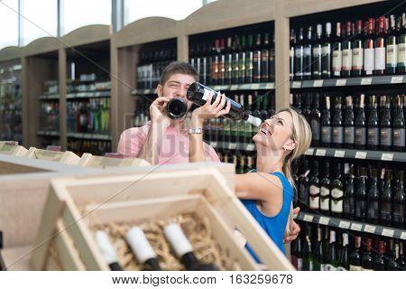 Woman Drinking Wine In Supermarket