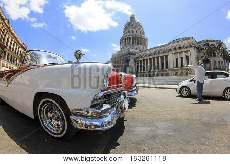 Classic old American car in front of El Capitolio. Classic cars are still in use in Cuba and old timers have become an iconic view and a worldwide known attraction