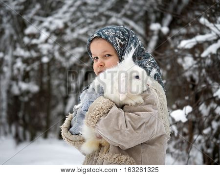 The little girl in the woods in winter with a lively fluffy white rabbit on hands