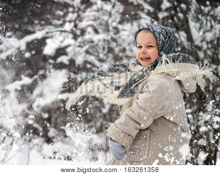 Happy child playing in the snow. A lot of flying snow flakes the girl laughs. Winter