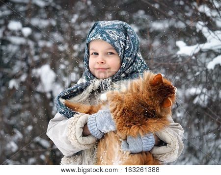 Little girl under falling snow with a huge ginger cat on the hands