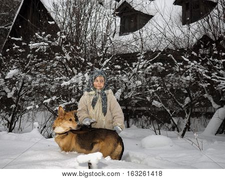 little girl with a dog in large snow drifts. Winter. Girl in a scarf and coat