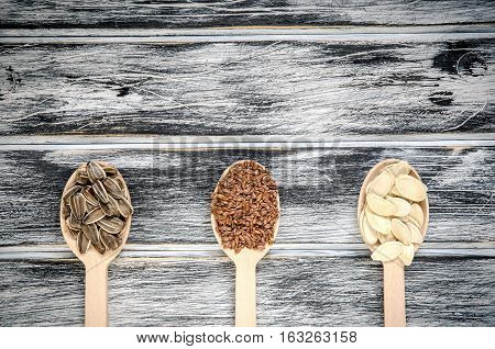 Sunflower linseed and pumpkin seeds in wooden spoons.