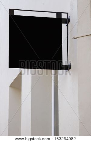 Black mock up. Square shape signboard on wall.