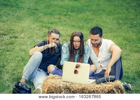 Anxious friends people pretty girl and handsome men watch laptop computer outdoors on natural background