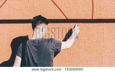 Man writing graffiti on the urban walls