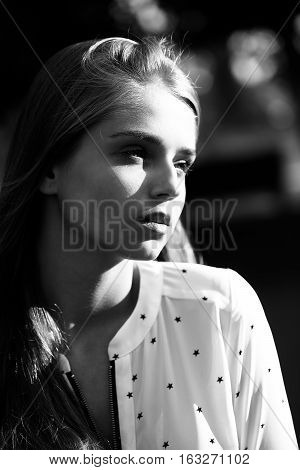 Pretty cute young woman or girl with long blonde hair in blouse with stars with serious face outdoor black and white