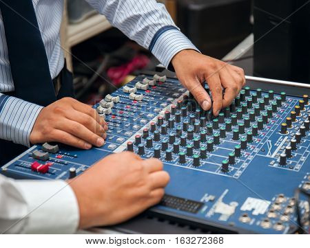 man hands tuning of sound mixer. stock photo