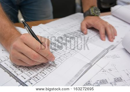 Closeup of man's hands holding blueprints at construction site