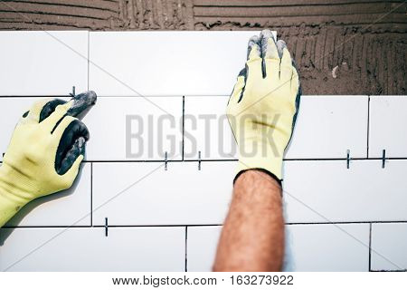 Industrial Worker Hands Installing Ceramic Tiles On Interior Walls, Handyman Using Plastic Distancer
