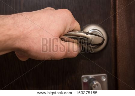 Closeup of hand holding metal silver doorknob on wooden door
