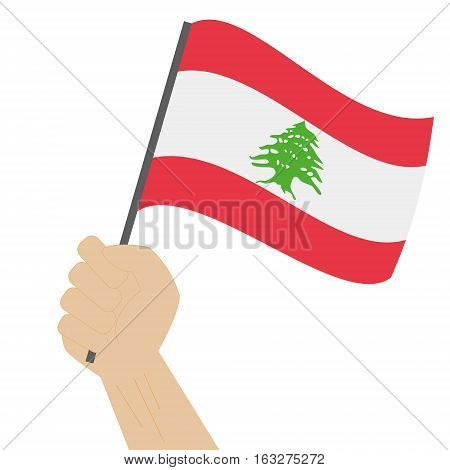 Hand holding and raising the national flag of Lebanon
