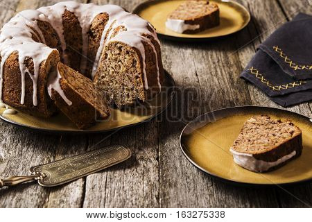 Banana cake with apples and walnuts drizzled frosting and sliced pieces on plates with effect craquelure on the shabby wooden background. Selective focus