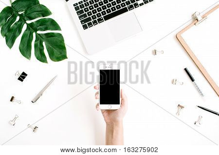 Mockup of smartphone with black screen in female hand. Flat lay top view workspace