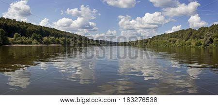 Summer landscape with river and clouds over the water.