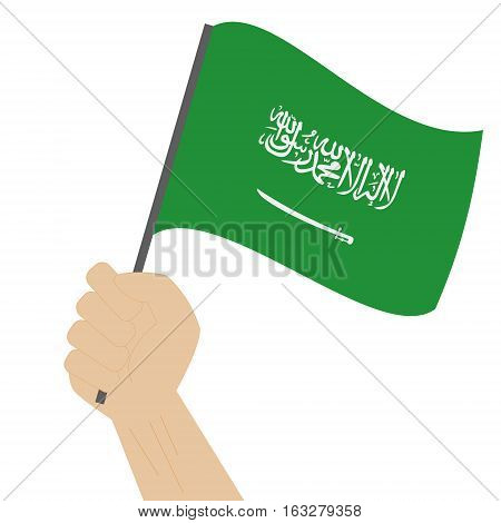 Hand holding and raising the national flag of Saudi Arabia
