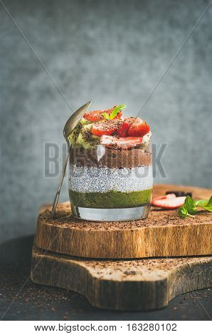 Healthy detox breakfast concept. Matcha, almond milk, cocoa chia seed pudding with fresh fruit, berries, mint, chocolate in glass over wooden board, grey wall background, selective focus, copy space