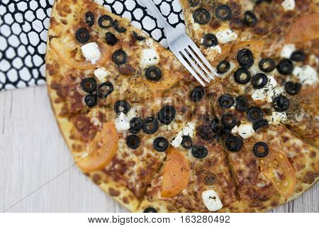 Grilled pizza with chees and black olives on the modern design tea towel and white wooden background. Top view