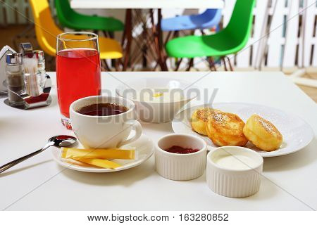 Table set for breakfast with rice porridge, cheesecakes with jam, berry drink and tea in cafe