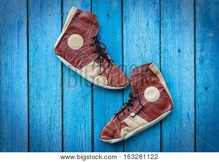 Vintage leather shoes for wrestling blue wood background