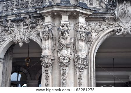 Close-up of sandstone sculptures of satyrs as atlantes on the pilasters of pylon of entrance under Rampart pavilion in Dresden Saxony Germany.