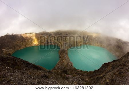 Tricoloured lakes in caldera of Kelimutu Volcano covered by clouds Flores Island Indonesia