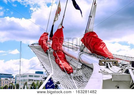 Details of bowsprit and gathered red sail of the tall ship on the cloudy sky background. Hanse Sail.