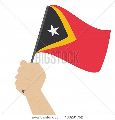Hand holding and raising the national flag of Timor Leste