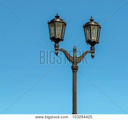 Old vintage street light against blue sky