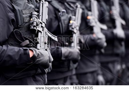 Soldier hand in black glove holding automatic machine gun during a military parade