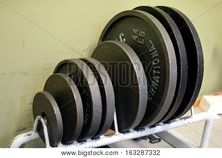 Barbell weight plates in rack on the gym.