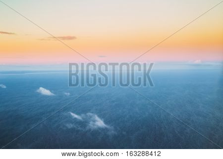 Aerial View From High Altitude Flight Of Aircraft On Baltic Sea, Gulf of Riga Surface In Winter At Sunset Sunrise. Clear Sunny Dawn Sky With Cold And Warm Colors.