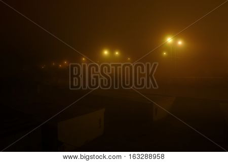 Chomutov Ustecky kraj Czech republic - November 17 2016: lamplight in thick fog above the garages and road number 13 during the upcoming evening