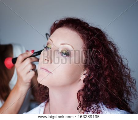 Red-haired lovely girl in a hairdressing salon makes a professional make-up