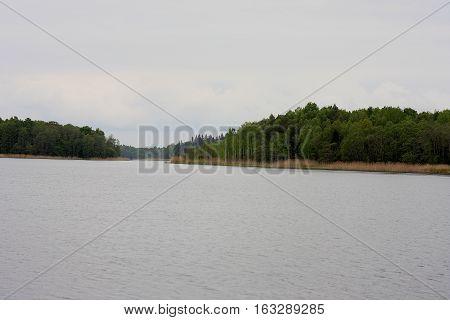 Belarussian spring landscape: huge lake and forest island on cloudy sky background