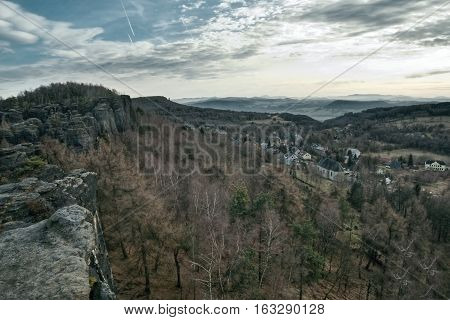 view from rocks to village Tisa in czech Krusne hory mountains in winter without snow