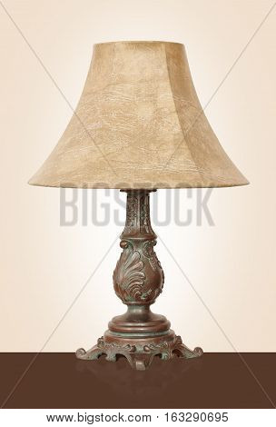 Light fixture - Vintage Desk lamp with the powerful brass basis on a beige background