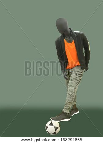 Full-length male mannequin dressed in sport athletics clothes with soccer ball isolated on green background. No brand names or copyright objects.