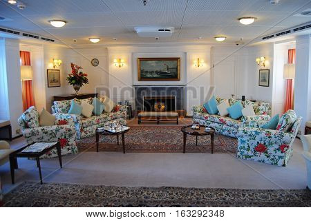 Edinburgh, United Kingdom - June 16, 2014. Drawing Room at the Royal Yacht Britannia. This is Britannia's main reception room which was also used by the Royal Family for relaxing, conversation and games. View with furniture, carpets, drawings and lamps.