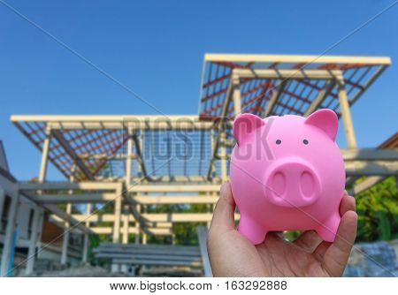 Male Hand Holding A Pink Piggy Bank On Blured Construction House Background