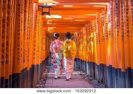 Kyoto, Japan - December 13, 2014: Two geishas walking through orange gates called torii at the Fushimi Inari Shrine