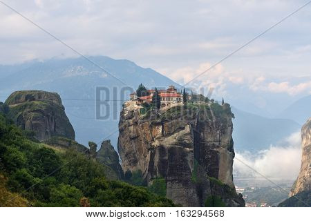 Meteora monasteries. Beautiful view on Monastery of the Holy Trinity placed on the edge of high rock covered of the morning at sun rises Kastraki Greece