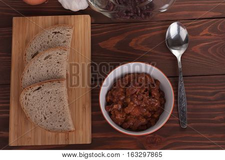 Chili Con Carne in pan on wooden table on background onion garlic bread and beans