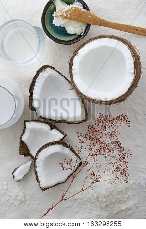 Pieces of a whole coconut cracked open on a white background. Coconut milk, water, flakes and oil are placed around the raw coconut in the center.