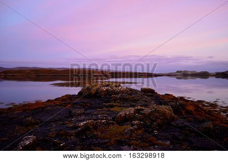 Pink and purple skies over Dunvegan Loch in Scotland.