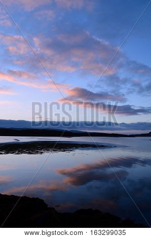 Pastel clouds reflecting in Loch Dunvegan in Scotland.