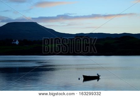 Solitary silhouetted dinghy boat on Loch Dunvegan in Scotland.